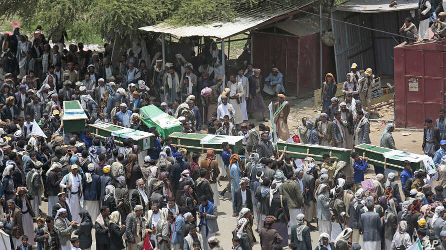 Yemeni people carry the coffins of victims of a Saudi-led airstrike, during a funeral in Saada, Yemen,  Aug. 13, 2018.