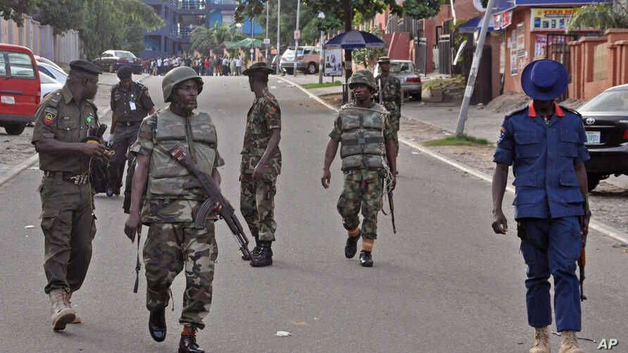 Nigerian soldiers patrol the area near the scene of a shopping mall explosion in Abuja, Nigeria, June 25, 2014.