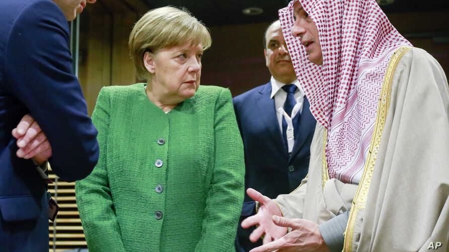 FILE - German Chancellor Angela Merkel, center, speaks with Saudi-Arabia's Foreign Minister Adel al-Jubeir, right, during a round table meeting of the EU-Sahel at EU headquarters in Brussels.