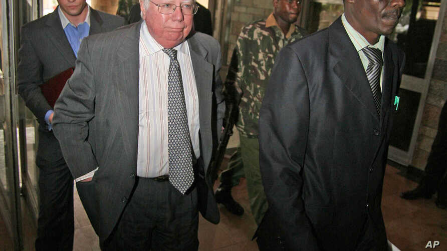 "FILE - Jerome Corsi, center, who wrote ""The Obama Nation: Leftist Politics and the Cult of Personality, follows an immigration department officer holding his passport."