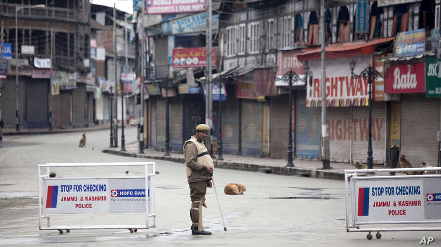 An Indian policeman stands guard at a temporary checkpoint during a curfew in Srinagar, India, March 14, 2013.