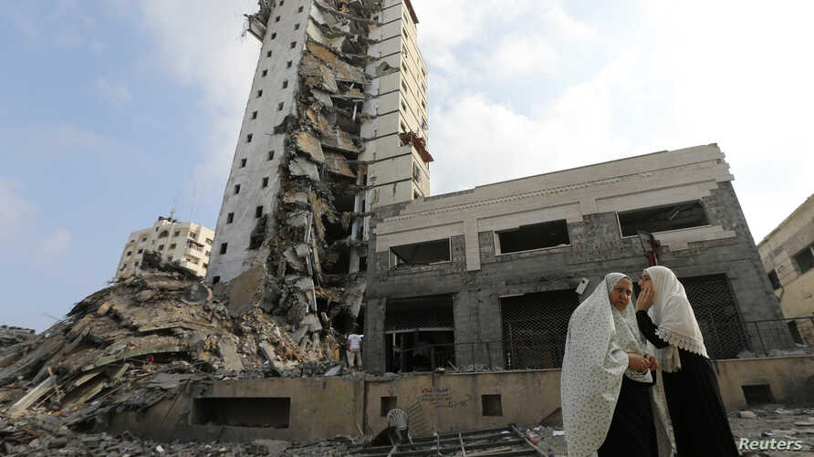 Palestinian women stand next to the remains of one of Gaza's tallest apartment towers, which was hit by an air strike that destroyed much of it, in Gaza City ,August 26, 2014.