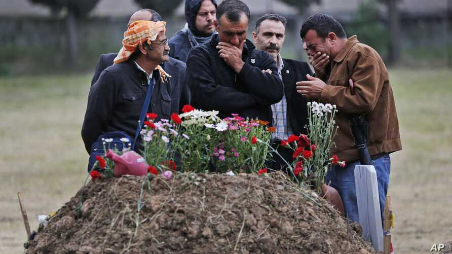 Relatives of a victim of the mine accident stand next to the grave of their loved one, in Soma, Turkey, May 17, 2014.