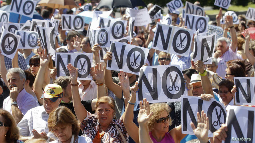 Civil servants hold up placards as they protest against government austerity measures in Madrid, July 23, 2012.