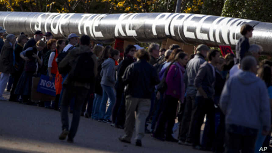 Demonstrators march with a replica of a pipeline during a protest to demand a stop to the Keystone XL tar sands oil pipeline outside the White House on Sunday, Nov. 6, 2011, in Washington.