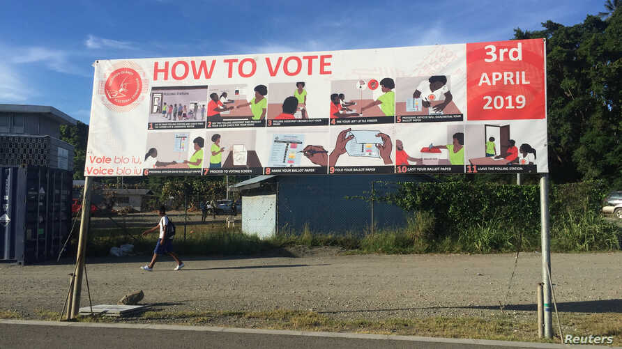 FILE - A boy walks past a sign with voting instructions on his way to school in Honiara, Solomon Islands, March 11, 2019.