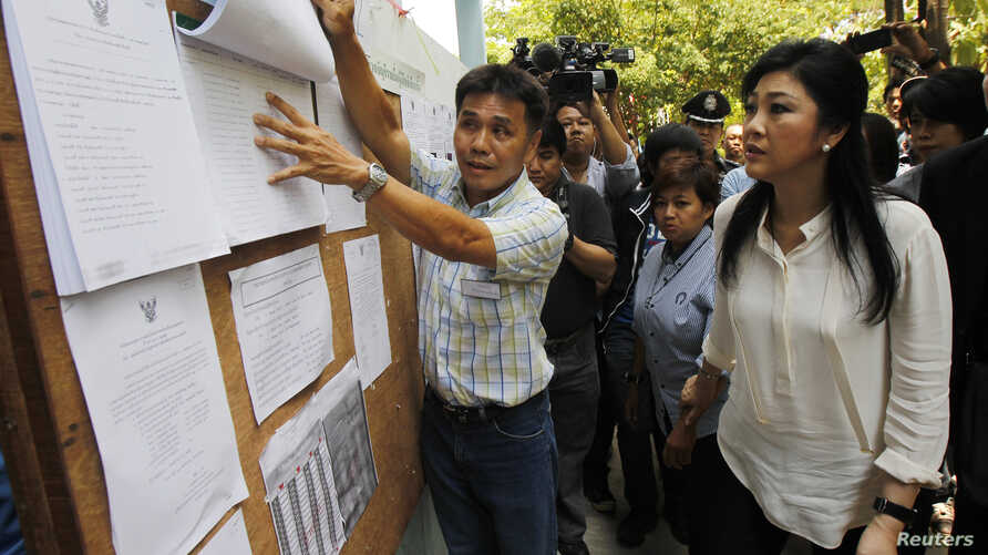 Thai Prime Minister Yingluck Shinawatra (R) checks a list of voters' names before voting at a polling station in Bangkok March 30, 2014. Thais voted on Sunday for half of the country's 150-seat Senate in a key test for Yingluck's troubled government,...