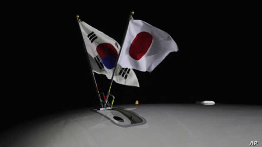 South Korean (L) and Japanese national flags fly on an airplane carrying Japanese Prime Minister Yoshihiko Noda upon his arrival at a military airport in Seongnam, near Seoul, October 18, 2011.