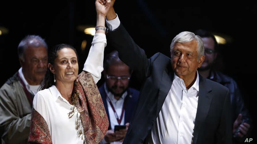 Presidential candidate Andres Manuel Lopez Obrador, of the MORENA party, right, and Mexico City mayoral candidate Claudia Sheinbaum hold their closing campaign rally at Azteca stadium in Mexico City, Wednesday, June 27, 2018.