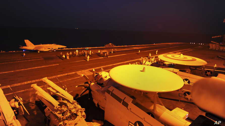 FILE- In this file photo released by the U.S. Navy on Sept. 23, 2014, A-18C Hornet, attached to Strike Fighter Squadron (VFA) 87, prepares to launch from the flight deck of the aircraft carrier USS George H.W. Bush.