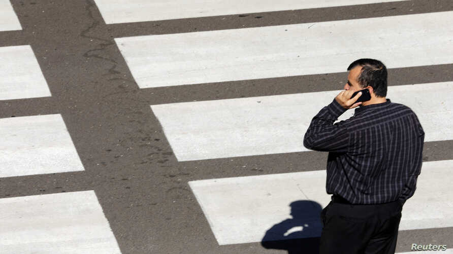 A man talks on his mobile phone as he waits at a crosswalk at Lindbergh Field Airport in San Diego, Calif.,  Nov. 6, 2013.