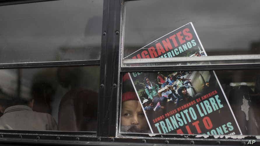 A Central American child who is traveling with a caravan of migrants, peers from a bus carrying the group to the U.S. border in Tijuana, Mexico, April 29, 2018. The sign reads in Spanish: We're all brother countries from the Americas. Free transit. S