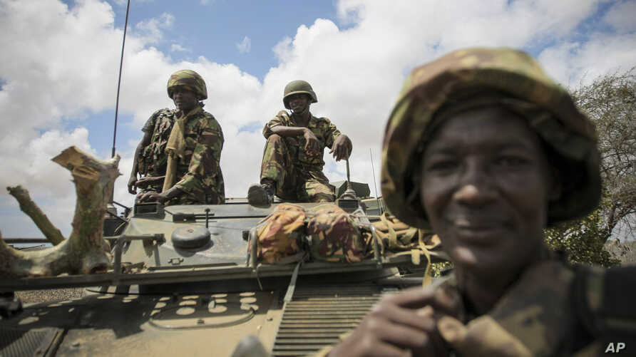 In this photo released by the African Union-UN Information Support Team, Kenyan soldiers with the African Union Mission in Somalia sit on top of an armored vehicle in Saa'moja, north-west of the port city of Kismayo, October 1, 2012.