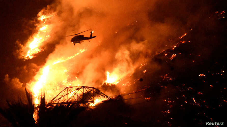 A Los Angeles County fire helicopter makes a night drop while battling the so-called Fish Fire above Azusa, California, June 20, 2016.