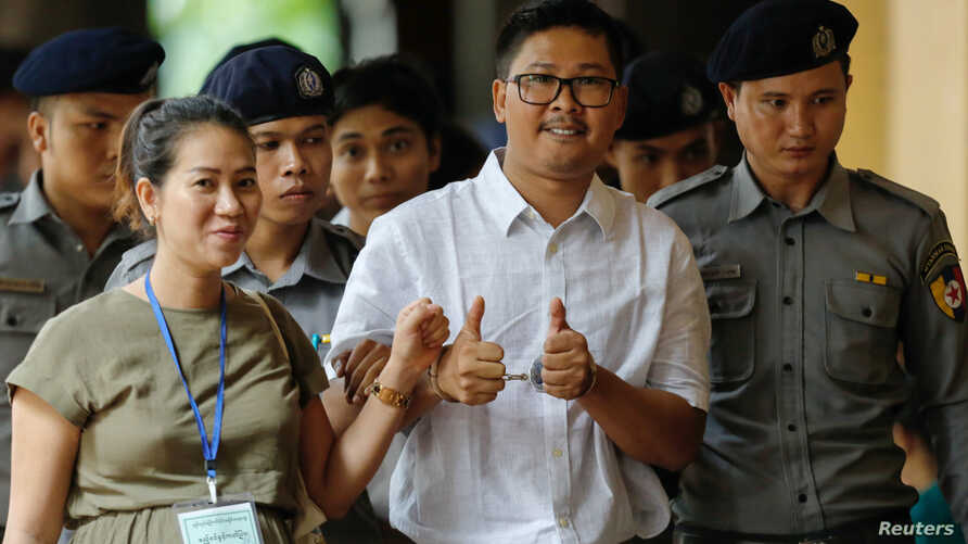 Detained Reuters journalist Wa Lone walks with his wife Pen ei mon as he arrives at Insein court in Yangon, Myanmar, July 23, 2018.
