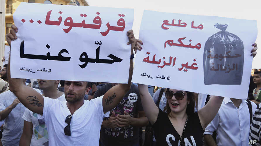 Protesters hold up signs against the Lebanese government during a rally against the ongoing trash crisis, in downtown Beirut, Lebanon, Aug. 8, 2015. The sign at left reads in Arabic 'We're sick of you, go away' and, at right, 'Nothing comes from you