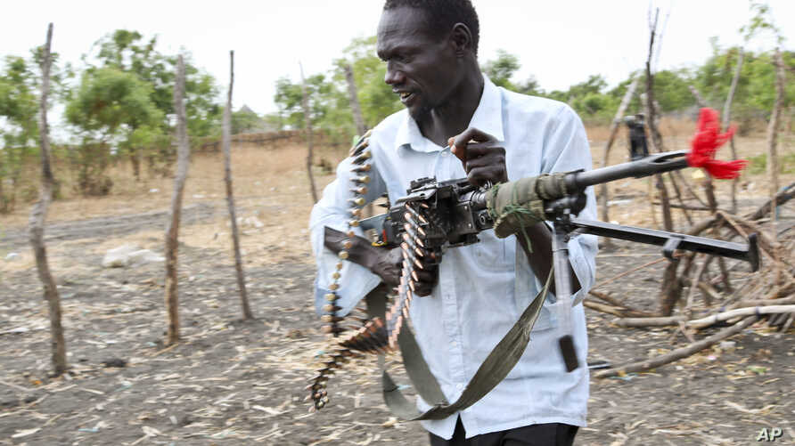 An opposition fighter walks with his weapon on which is tied a red ribbon, signifying danger as a warning to government forces and a willingness to shed blood, according to an opposition spokesman, in Akobo town, South Sudan, Jan. 21, 2018..