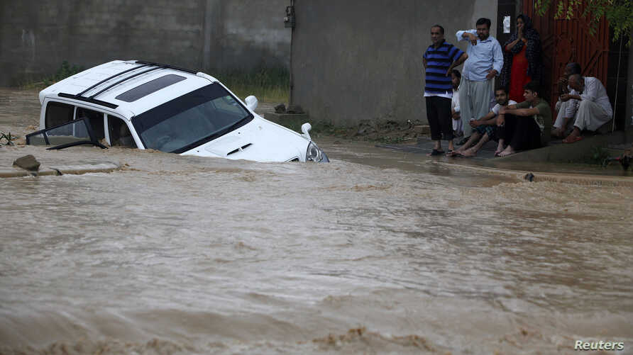 Family members wait for rescue workers after their vehicle was submerged in flood waters on the outskirts of Karachi, Pakistan, August 4, 2013.