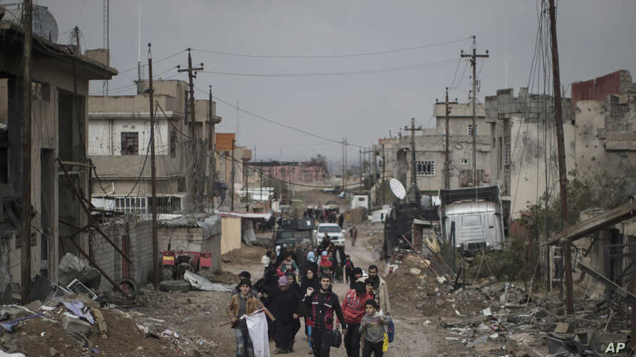 FILE - Iraqi civliians flee their homes during fighting between Iraqi security forces and Islamic State militants, on the western side of Mosul, Iraq, March 13, 2017.