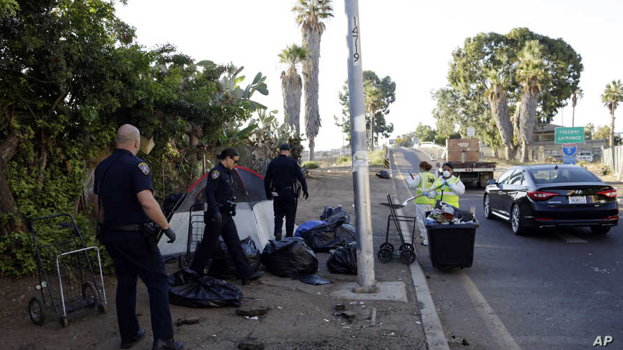 FILE - In this Sept. 25, 2017, photo, police officers remove a tent left by homeless people during efforts to sanitize neighborhoods to control the spread of hepatitis A, in San Diego.