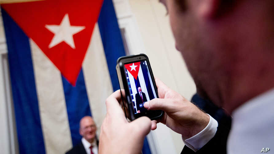 A visitor poses for a photograph in front of the last Cuban flag that was lowered from the Cuban Embassy in Washington on Jan. 3, 1961 when relations between the United States and Cuba were severed, in their new embassy in Washington, July 20, 2015.