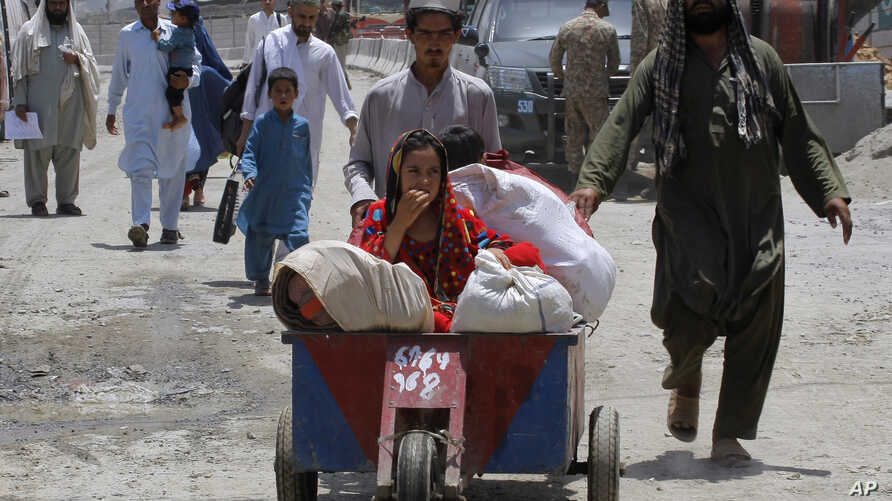 Afghan families arrive at the border crossing in Torkham, Pakistan, Saturday, June 18, 2016.