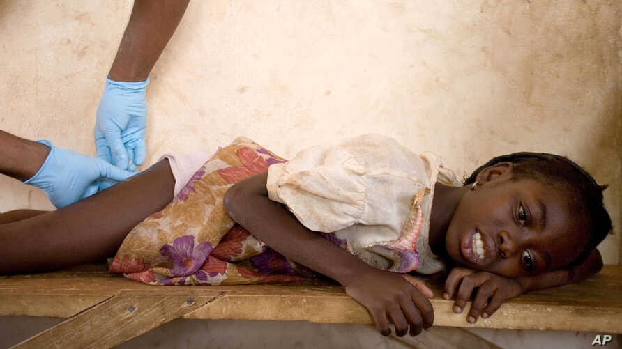 FILE - A girl grimaces as a health worker extracts a parasitic worm from her at a containment center in Savelugu, Ghana.