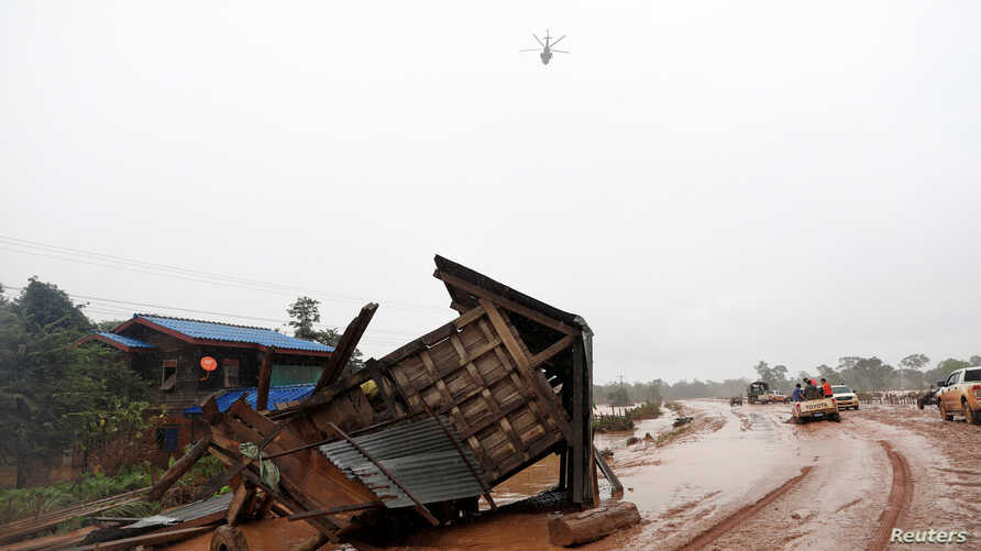 A military helicopter flies during the flood after the Xe Pian-Xe Namnoy hydropower dam collapsed in Attapeu province, Laos, July 26, 2018.