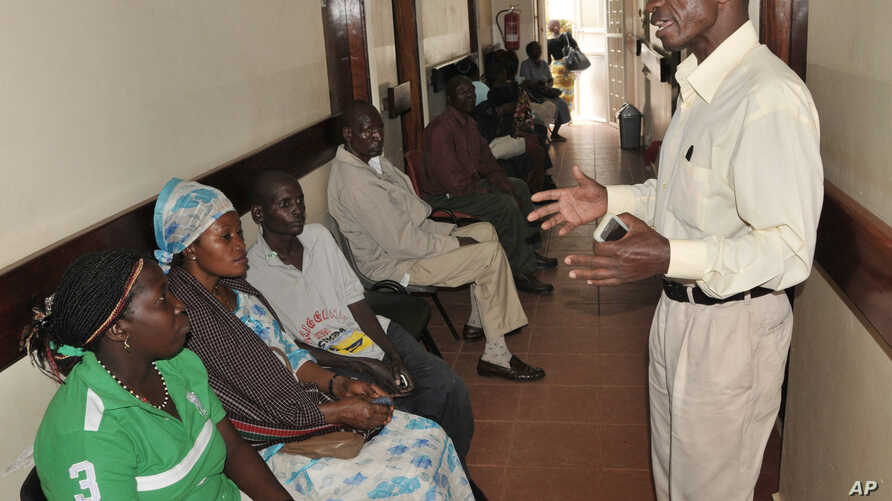 FILE - A health worker from The AIDS Support Organization (TASO) speaks with patients waiting for treatment in Kampala, Uganda.