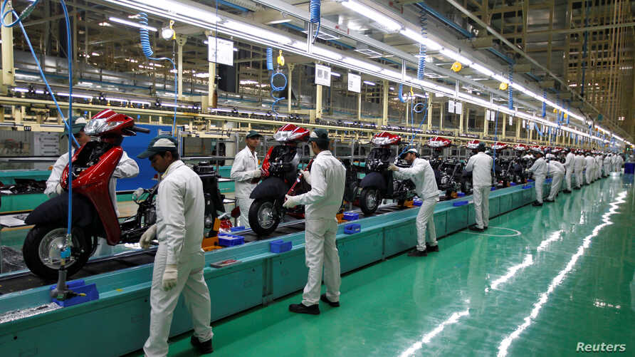 Employees work on an assembly line of Honda Motorcycle & Scooter India during a media tour to the newly inaugurated plant at Vithalapur town in the western state of Gujarat, India, Feb. 17, 2016.