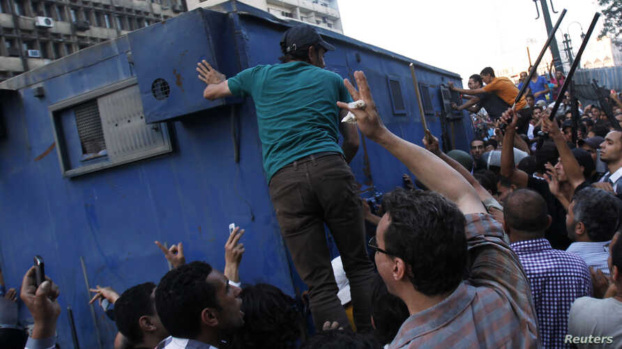 Supporters of the interim government installed by the army gather around a police van carrying Muslim Brotherhood supporters from the al-Fath mosque on Ramses Square in Cairo, Egypt, Aug. 17, 2013.