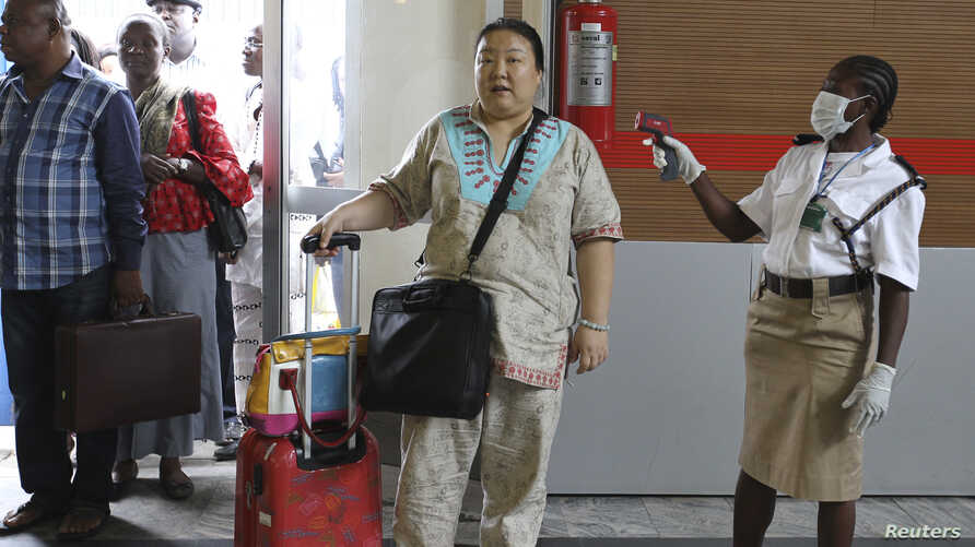 A female immigration officer uses an infra-red laser thermometer to examine a passenger at Nnamdi Azikiwe International Airport in Abuja, Nigeria, Aug. 11, 2014.