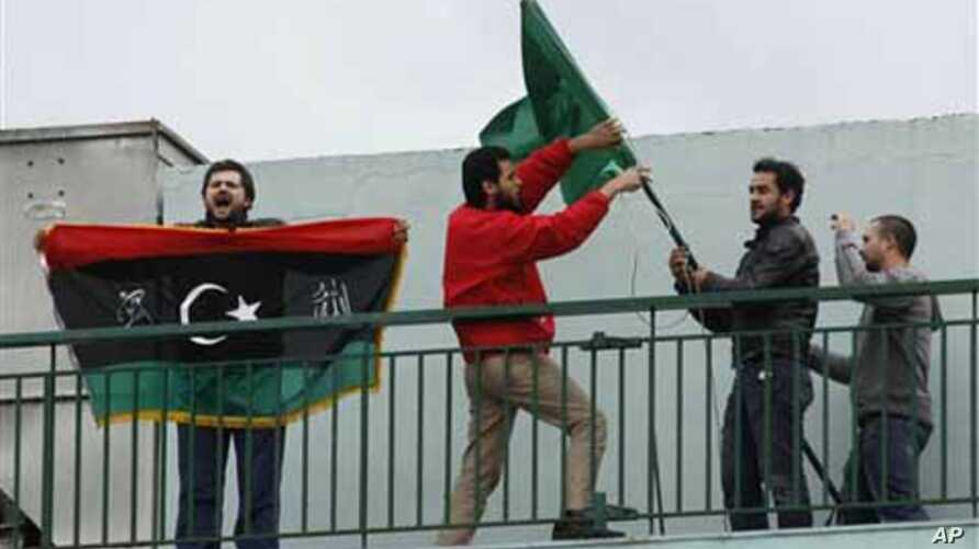Libyans who live in Greece remove the Libyan flag from a Libyan state school as another shouts slogans and holds the old flag of his country during a protest in Athens, Tuesday, Feb. 22, 2011. About 60 Libyans gathered at the protest against Gadhafi'
