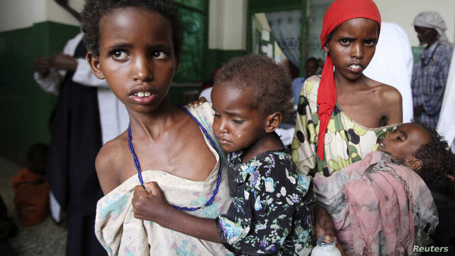 Girls carry their malnourished siblings in Banadir hospital, south of capital Mogadishu August 28, 2011.