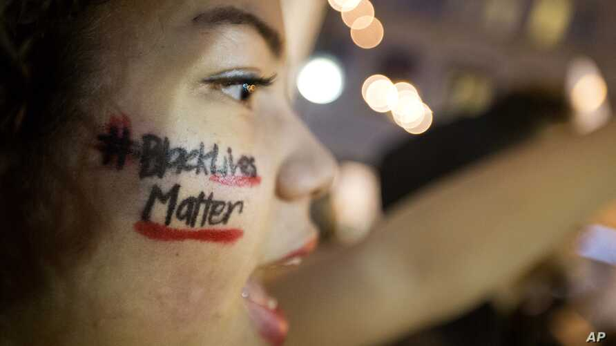 """FILE - A woman with """"Black Lives Matter"""" written across her cheek attends an ATlanta demonstration against the deaths of unarmed black men at the hands of white police officers."""