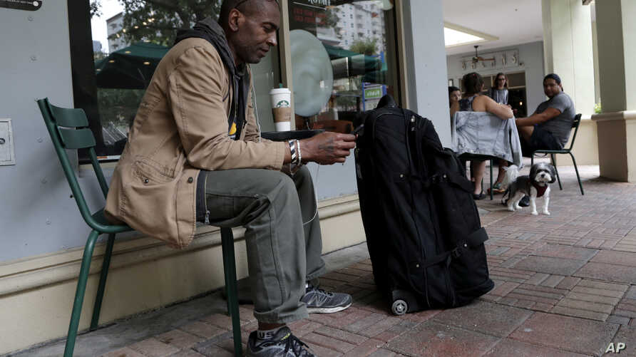 Darnell Metcalf, 55, a regular customer of Starbucks, sits outside of the store after it closed temporarily, May 29, 2018, in Miami.