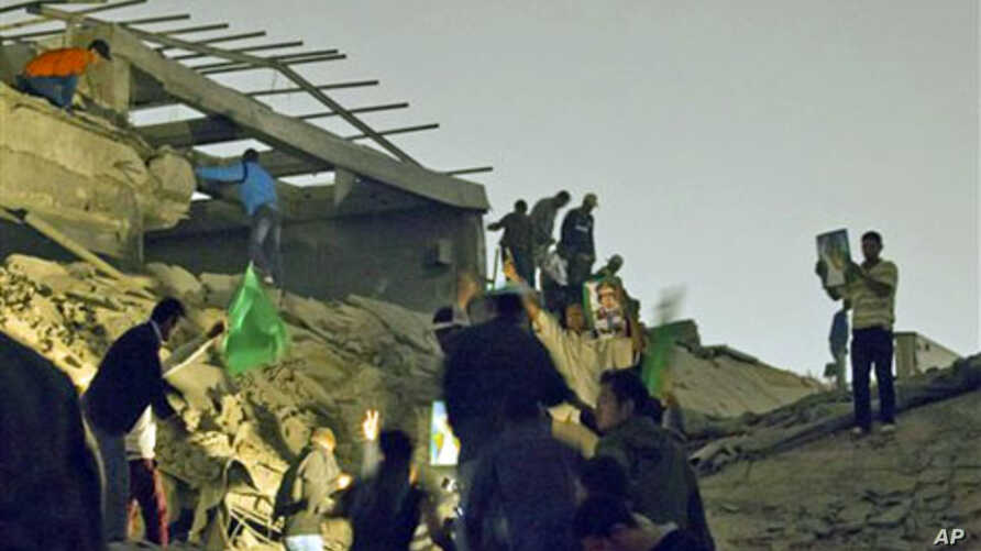 Moammar Gadhafi supporters inspect damage following an airstrike in Tripoli, Libya. The airstrike on Gadhafi's sprawling residential compound early Monday badly damaged two buildings, including a structure where Gadhafi often held meetings, guards at