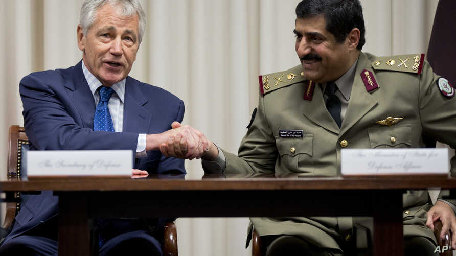 Defense Secretary Chuck Hagel, left, shakes hands with Qatari Defense Minister Hamad bin Ali al-Attiyah during a signing ceremony at the Pentagon, July 14, 2014.
