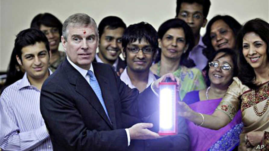 Britain's Prince Andrew, second left, holds a solar lamp as students and teachers look on during his visit to H.R. College of Commerce and Economics in Mumbai, India (file photo – 09 Mar. 2010)