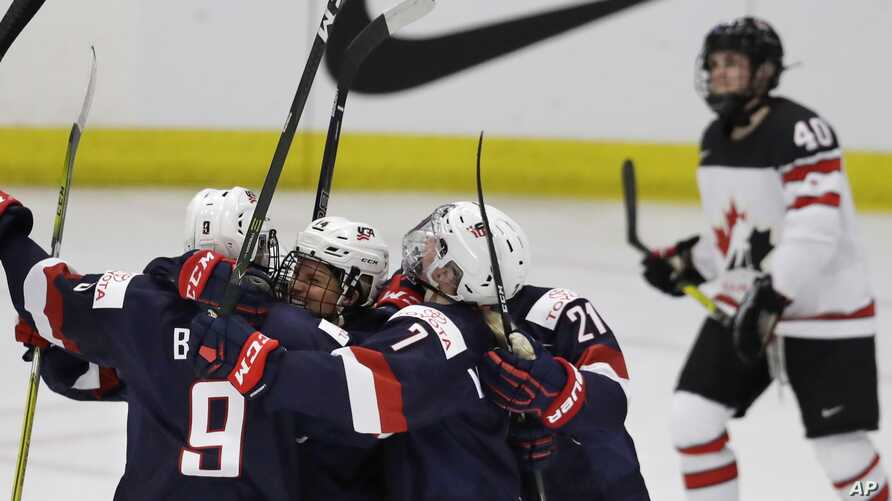 United States forward Brianna Decker is surrounded by teammates after scoring during the second period of a IIHF Women's World Championship hockey tournament game against Canada, March 31, 2017, in Plymouth, Mich.