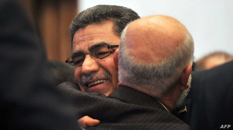 Syrian communications executive Ghassan Hitto (L), is congratulated late on March 18, 2013 in Istanbul after Syria's main opposition National Council elected him as prime minister.