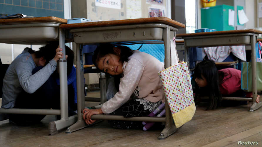 FILE - School children take shelter under desks during an earthquake simulation exercise in an annual evacuation drill at an elementary school in Tokyo, March 10, 2017.
