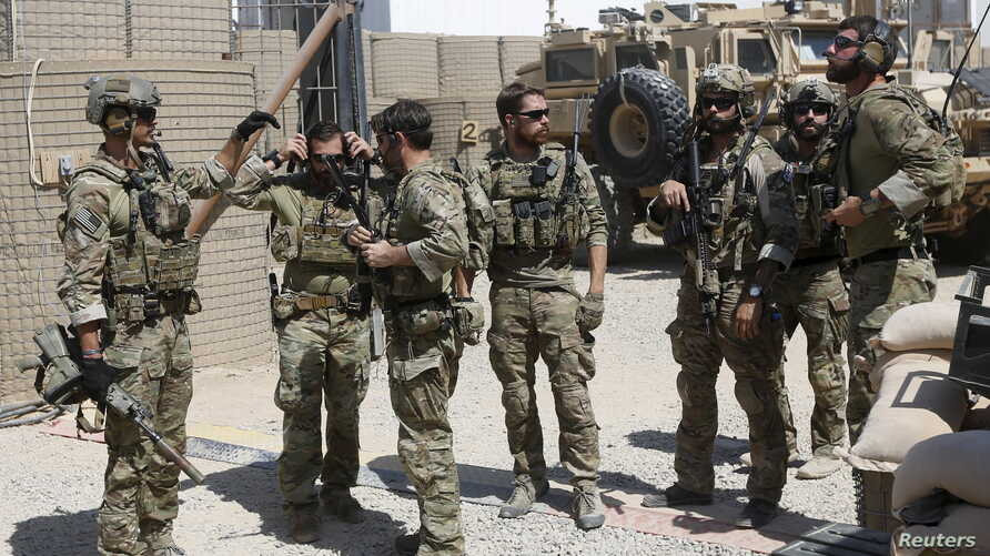 U.S. special forces soldiers talk to each other before they leave their base in Helmand, Afghanistan September 28, 2015.