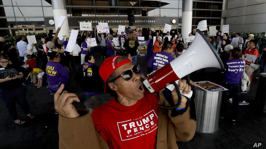 A supporter, foreground, of President Donald Trump yells as demonstrators chant outside Tom Bradley International Terminal during a protest, Jan. 30, 2017, at Los Angeles International Airport.