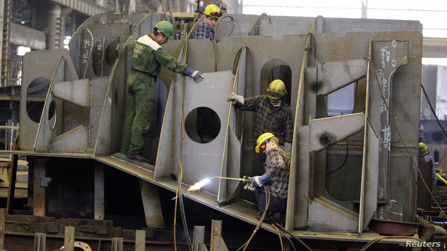 FILE - Workers assemble a part of a ship at a shipbuilding site at the Gdynia shipyard.