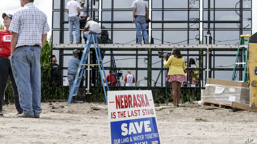 A sign against the Keystone XL pipeline is planted in the foreground, as workers and volunteers assemble solar panels in a corn field belonging to Jim Carlson, directly in the path of the proposed pipeline, in Silver Creek, Nebraska, July 29, 2017....