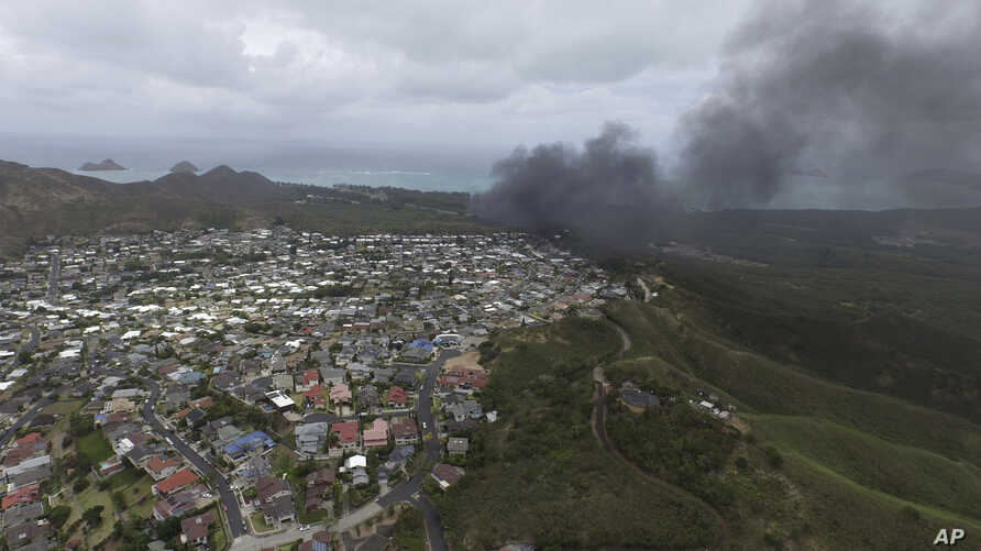 In this photo taken by a drone, smoke rises from a Marine Corps Osprey aircraft after it made a hard landing on Bellows Air Force Station near Waimanalo, Hawaii, Sunday, May 17, 2015.