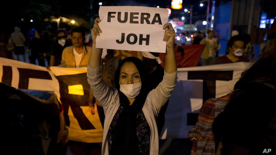 """A woman holds a sign with a message that reads in Spanish """"Get out JOH"""" during a protest against Honduran President Juan Orlando Hernandez, in Tegucigalpa, Honduras, Jan. 26, 2018. Hernandez was awarded the electoral win last month despite the disput"""