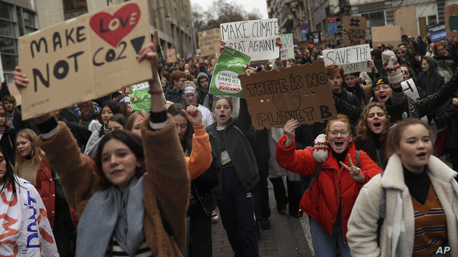 Youngsters hold up banners as they march during a protest against the climate change in Brussels, Belgium, Jan. 10, 2019.