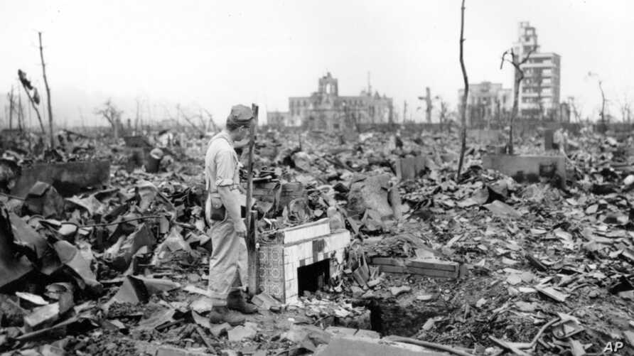 FILE - In this Sept. 7, 1945, photo, an unidentified man stands next to a tiled fireplace where a house once stood in Hiroshima, Japan. The Los Alamos Historical Museum recently announced it won't be hosting a Japanese traveling exhibit until the par
